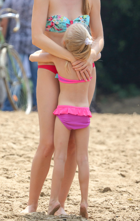 Mom and daughter in swimsuits on the beach.