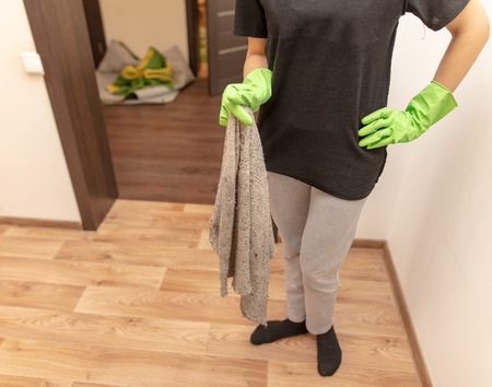 The girl washes the floor with a rag in the room. Stock Photo