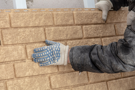 Installing brick siding on the wall of the house .