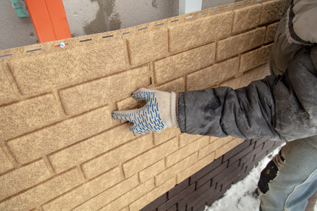 Installing brick siding on the wall of the house . Stock Photo - 121515119