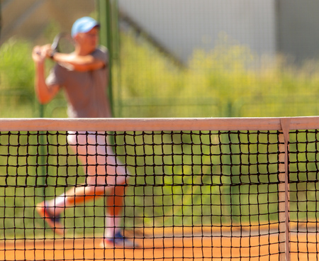 A man plays tennis on the court in the park .