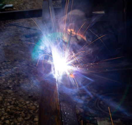 Sparks from welding at a construction site as a background. Imagens