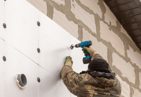 Worker insulates the walls of the house with plastic panels. Stock Photo