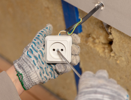 A worker installs a wall outlet.