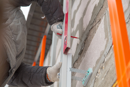 A worker installs a metal profile on the walls of a siding house.