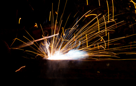 Sparks from welding at a construction site as a background.
