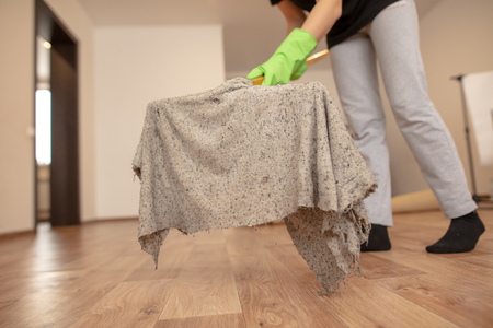 The girl washes the floor with a rag in the room.