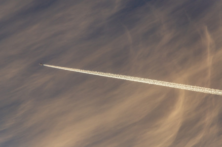 Trail from the plane in the sky at sunset.