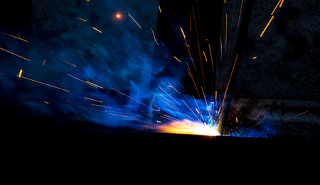 Sparks from welding at a construction site as a background. Фото со стока