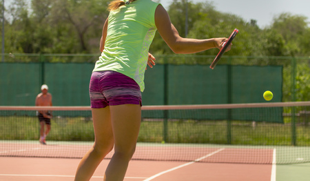 Girl playing tennis on the court in the open air .