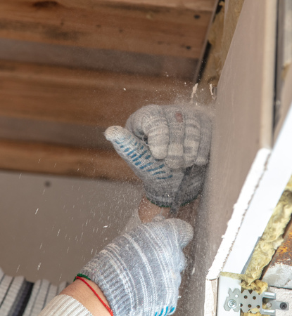 Worker cuts with a knife drywall repair.