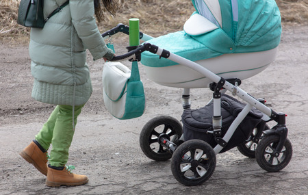 Girl with a stroller goes on the road in winter.
