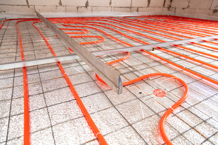 Installing a hose for underfloor heating in the room.