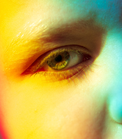 The eyes of the boy in the light of the rainbow .