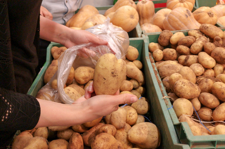 A girl buys potatoes on the counter in the store . Banco de Imagens