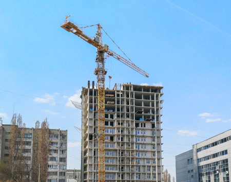 Crane builds a tall house against the blue sky .