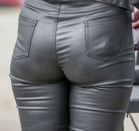 Leather pants on the legs of the girl .