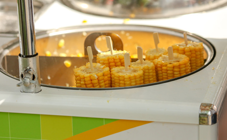 Corn is boiled in a pan in the market .