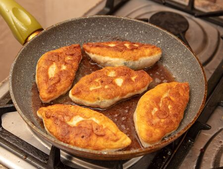 Patties are fried in oil in a pan .