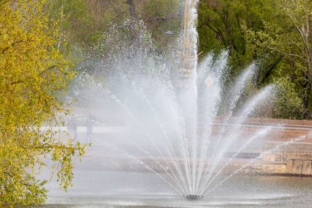 Splashing water from a fountain in the park . Фото со стока