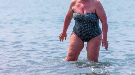 Mujer con sobrepeso en traje de baño en agua de mar.