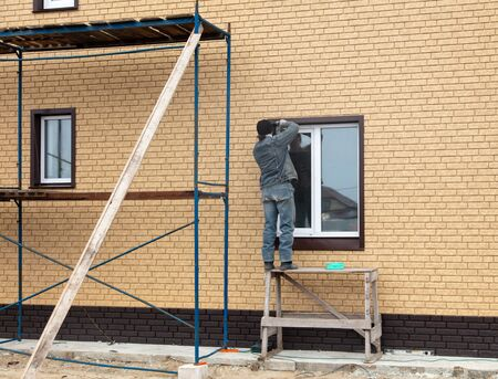 The worker installs a metal window in the house .