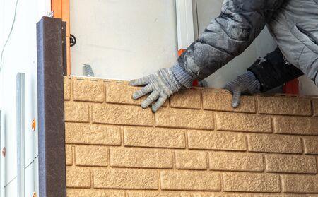 Worker installs plastic panels with bricks . Stock Photo - 126304395