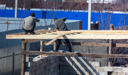Workers build a roof of wood in the house .