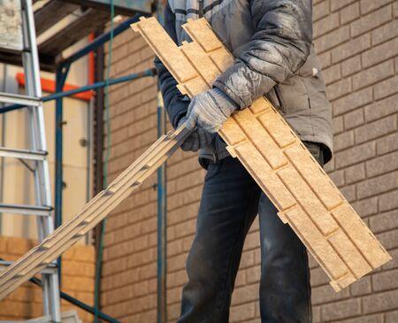 Worker installs plastic panels with bricks .