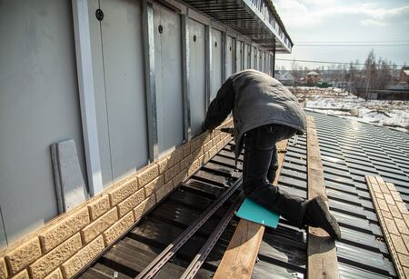 Worker installs plastic panels with bricks .