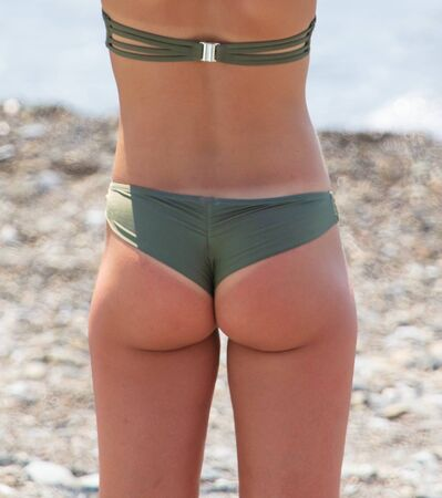 Hermosa chica a tope en la playa. Parte del cuerpo humano. Vacaciones de verano en el mar