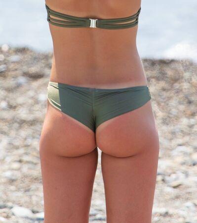 Schönes Hinternmädchen am Strand. Teil des menschlichen Körpers. Sommerurlaub auf See