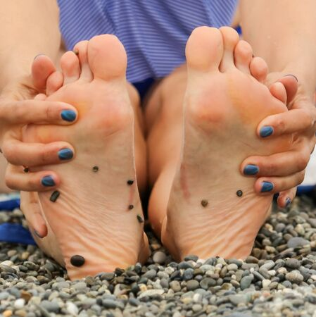 Feet girls on the beach with pebbles. Vacation at sea. Standard-Bild - 129138356