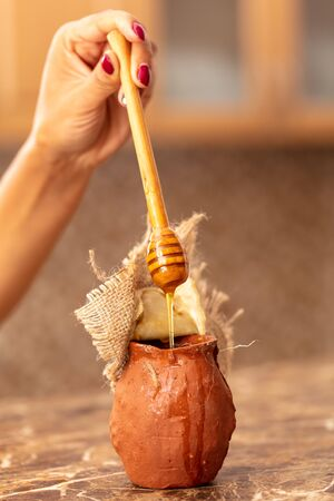 Honey in clay pots on a wooden spoon . Imagens - 128461941