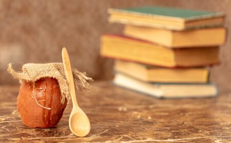 Honey in clay pots on the background of books . Imagens - 128461982