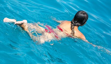 The girl swims in the water . Summer vacation at sea Standard-Bild