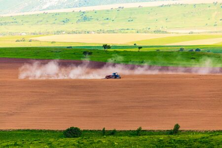 Dust from a tractor working in a field in spring .