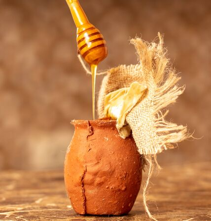 Honey in clay pots on a wooden spoon . Imagens - 128546230