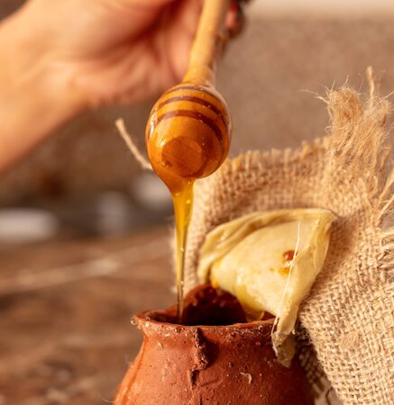 Honey in clay pots on a wooden spoon .