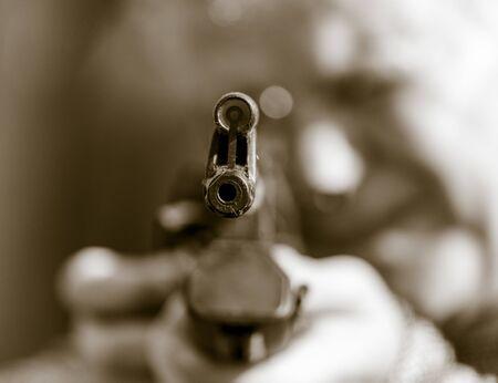 Ein Mann schießt mit einer Waffe. Schwarzweißfoto