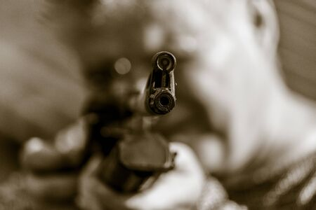 A man shoots with a gun. Black and white photo