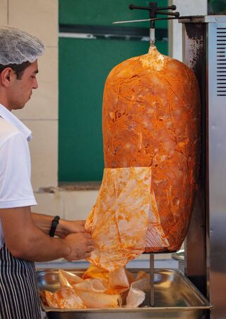 Bodrum, Turkey - August 21, 2019: A man cooks grilled chicken meat.