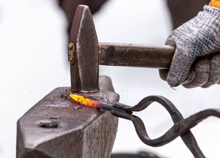 A blacksmith bends metal with a hammer.