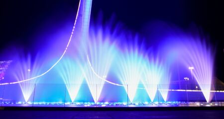 A dancing fountain of blue in the park. Splashing water. Stock Photo