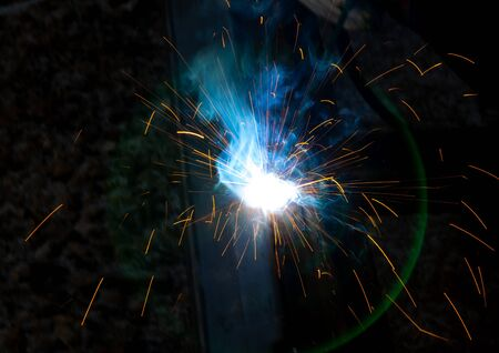 Sparks from welding at a construction site as a background. Stockfoto