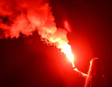 Red smoke bomb in a girl's hand at night.