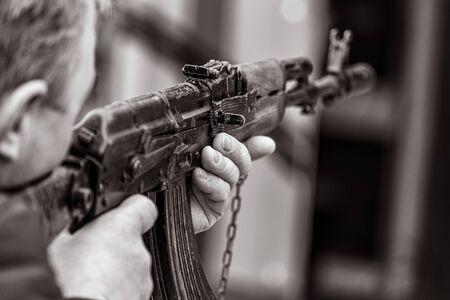 A man shoots with a gun. Black and white photo
