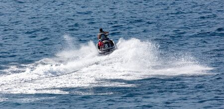 A motorcycle is racing in the blue water of the sea. Stok Fotoğraf