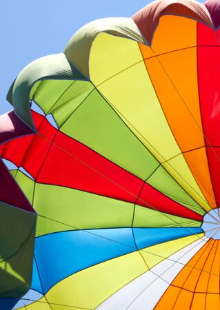 A multi-colored dome of a parachute in the sky as a background. 免版税图像