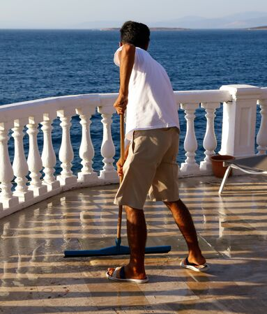A man washes the floor near the pool.